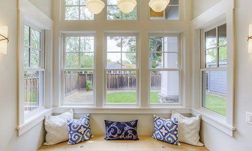 vista di alcune finestre in legno bianco e davanti un divano con dei cuscini