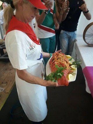 una cuoca con un piatto di astice gigante in mano