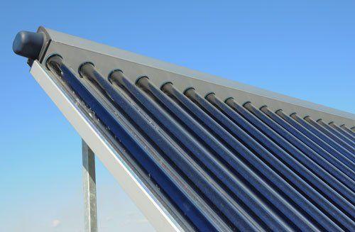 Tetto moderno della casa con riscaldatore solare dell'acqua, concetto di risparmio energetico.