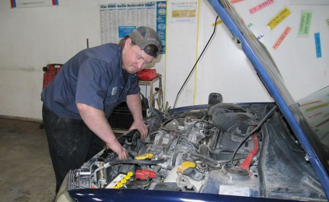Mechanic performing car repairs on an engine in Whangerei