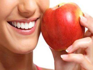 Donna che sorride con mela rossa