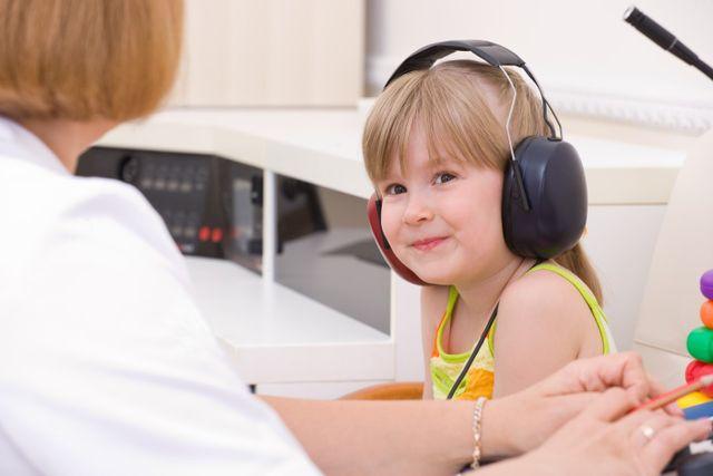 Una bambina sorridente effettua un controllo dell'udito con delle grandi cuffie