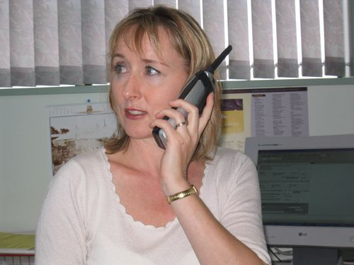Angela Morse talking with a client through phone