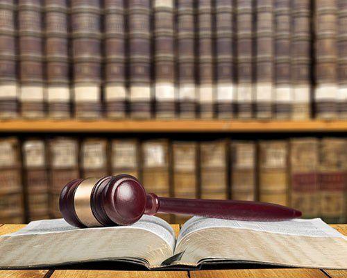 Il martello di giustizia su un libro aperto e di fronte ad una biblioteca piena di vecchi libri di leggi