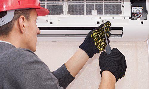 Operatore con elmetto e guanti usando un cacciavite