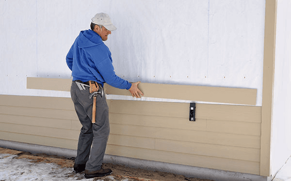 Carpenter using gauge to install fibrous cement siding in St. Peters