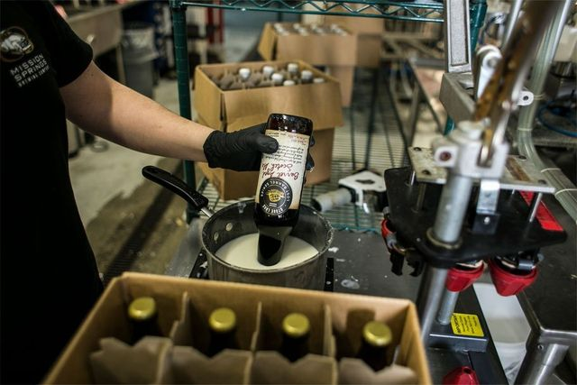 Strongman Ale bottles on assembly line