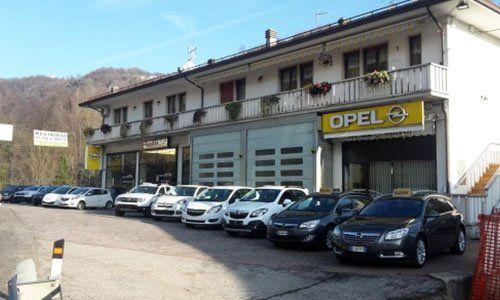 esterno della carrozzeria con logo Opel e una serie di macchine parcheggiate davanti a Recoaro Terme, VI