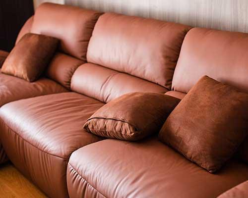 un divano di pelle con dei cuscini in camoscio