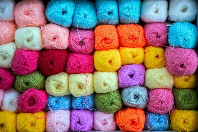 close up di gomitoli di lana di colore beige,bronzo e blu