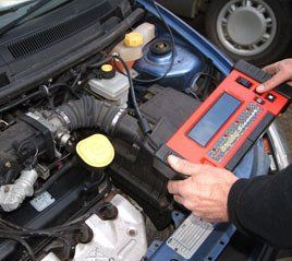 A mechanic using diagnostic equipment technology