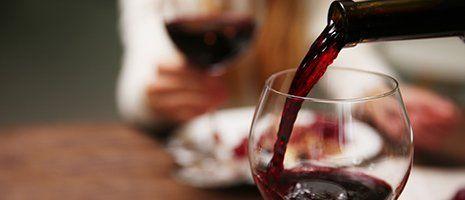 una bottiglia che versa del vino in un bicchiere