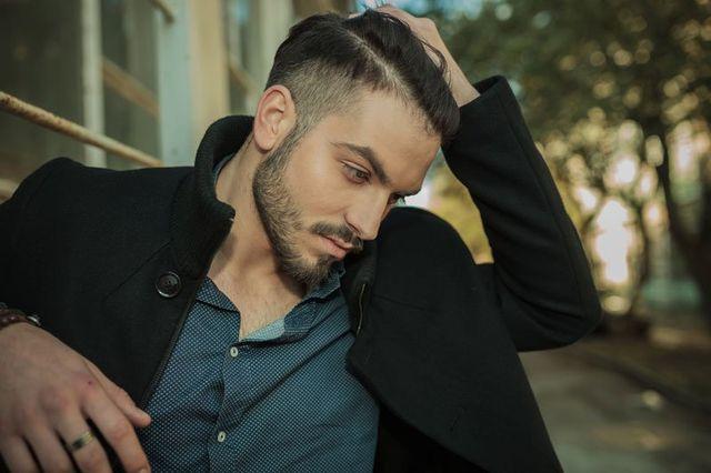 Un uomo con un cappotto nero e capelli con sfumatura