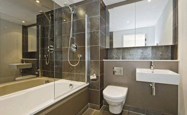 A stylish bathroom with shower over the bath and large black tiles on the walls