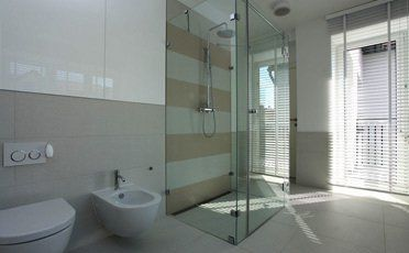 A spacious bathroom with a glass shower cubicle, bidet and toilet
