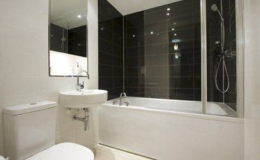 A shower over a bath in a stylish bathroom with black tiles