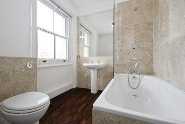 A large family bathroom with a shower over the bath, sink and toilet on a hardwood floor