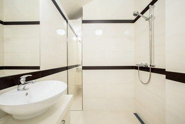 A stylish bathroom with cream tiles and a large sink