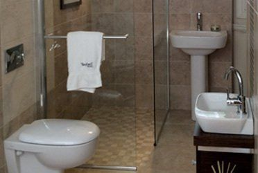 A small bathroom with a corner shower, sink and toilet