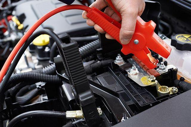 Uomo sta attaccando la pinza per caricare la batteria di un'auto