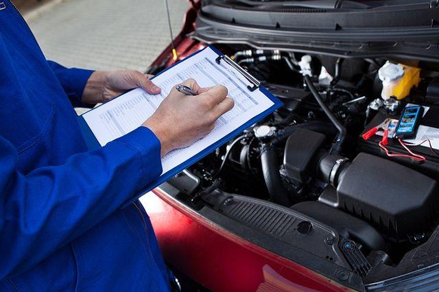 Meccanico prende nota su un  documento di fronte al motore di un'auto