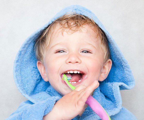 un bambino biondo con occhi azzurri con un accappatoio con il cappuccio azzurro mentre lava i denti