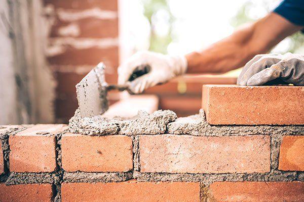 una mano con una spatola, del cemento fresco e dei mattoni