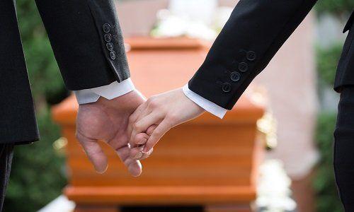 due mani che si tengono davanti a una bara