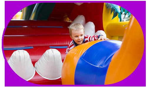 little boy playing in a bouncy castle
