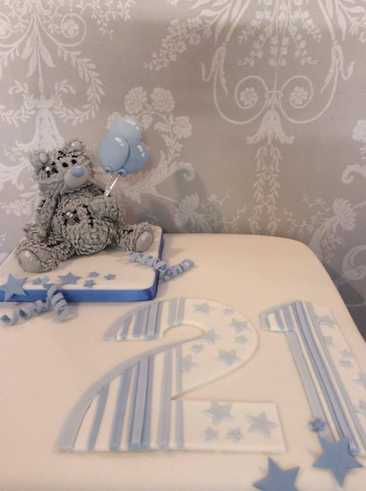 A blue and white 21st birthday cake with teddy bear decoration