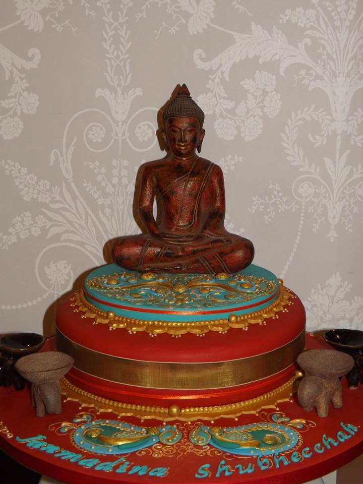 A red cake with a buddha sitting on top