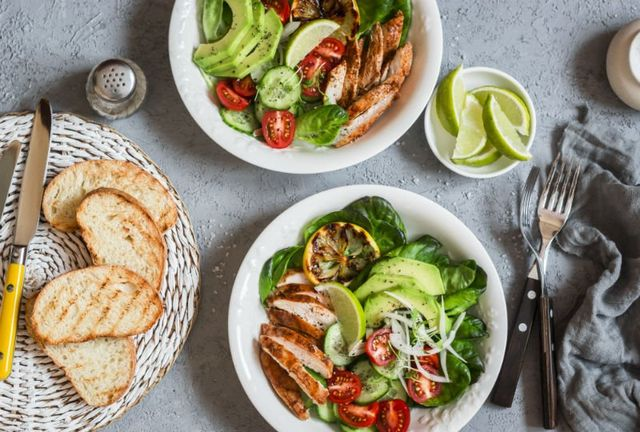 due piatti dell insalata con avocado, carne bianca e dei pomodorini