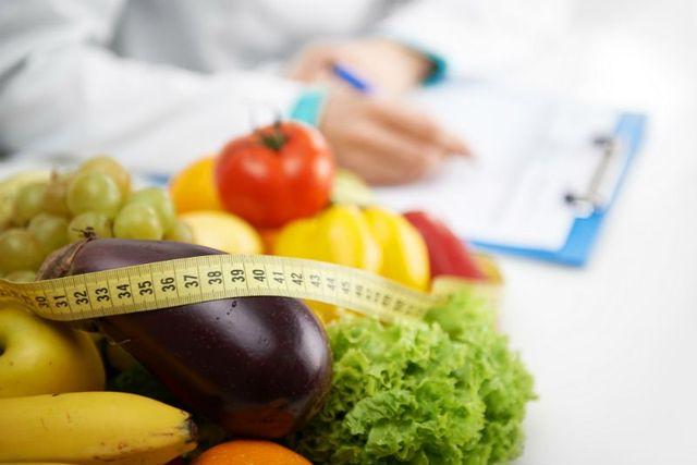 della frutta, verdura e accanto una nutrizionista mentre scrive su un rilievo di scrittura