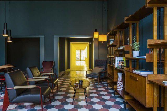 una sala con delle poltrone e una libreria in legno