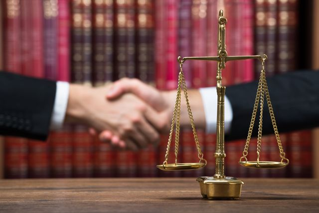 Handshake Behind Justice Scales In Library