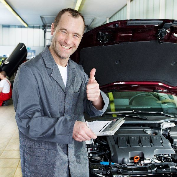 Happy auto mechanic performing a car inspection