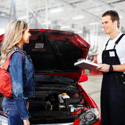 Auto mechanic and client discussing auto repairs