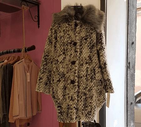 un cappotto da donna color beige con pelo intorno al collo e di fianco un appendiabiti con diversi capi appesi a Viterbo