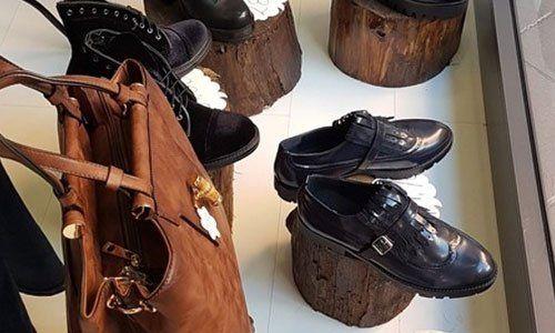 scarpe di pelle da donna e scarponcini di color nero messi su dei tronchi di legno e borsa di color marrone a Viterbo