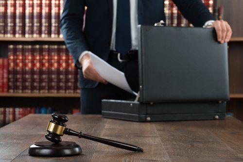 Avvocato con valigetta 24 ore e martelletto di un giudice su un tavolo