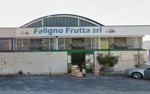 Vista dal'esterno di Foligno frutta srl con la porta d'entrata aperta, alcune cassette di legno appoggiate fuori e una macchina parcheggiata sulla destra
