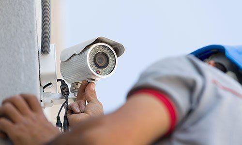 un impiegato sta installando una telecamera di sicurezza