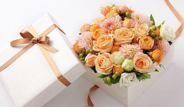una scatolina bianca con un fiocco marrone aperta e dentro delle rose arancioni-La primula di fiori e piante - Avellino