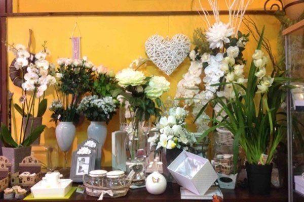 tavolo in legno scuro con vasi di fiori, oggetti e piccole scatoline bianche-La primula Fiori e piante- Avellino