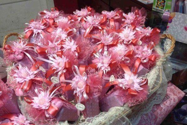 un cestino di paglia con dentro delle bomboniere con fiori e fiocchi rosa-La primula Fiori e piante-Avellino