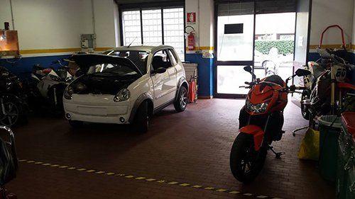 vista interna di autofficina con macchina e motociclette