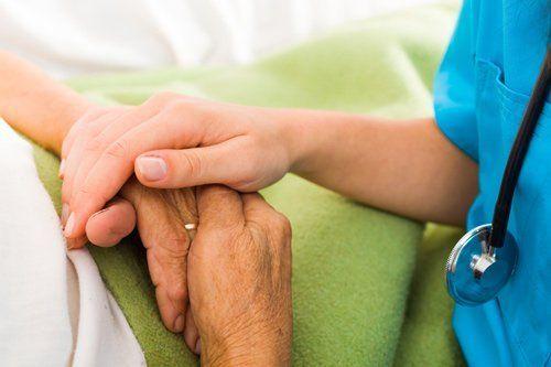 infermiera che stringe mano anziano