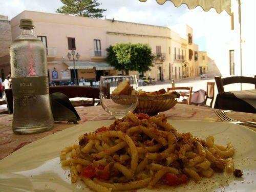un piatto di pasta, un bicchiere e un cestino di pane su un tavolo all'esterno del ristorante