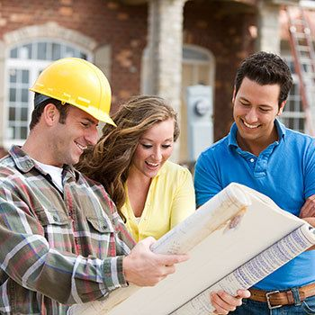 Couple and builder with new home construction blueprint near Cuba City WI