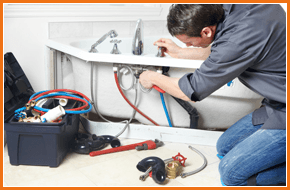 Plumber fitting a new tap onto a bath